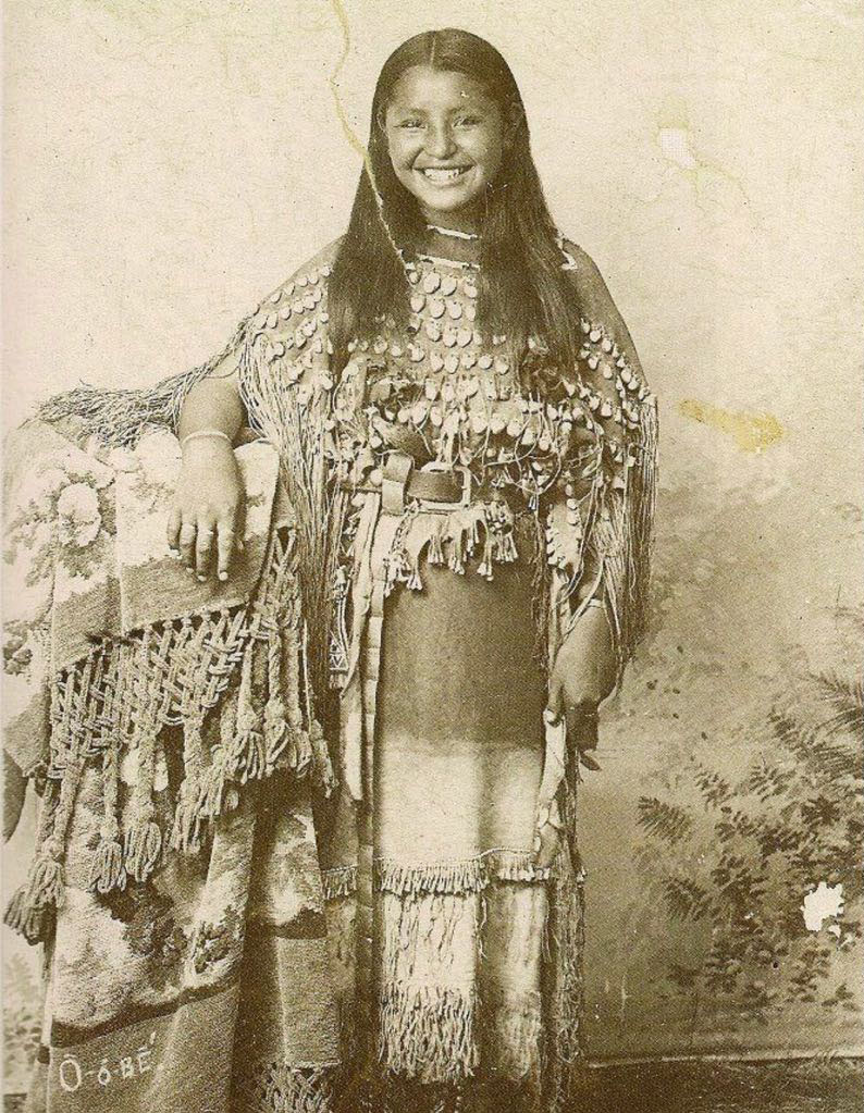 O-o-dee of the Kiowa tribe in traditional dress with a heartwarming smile on her face in a photograph over 100 years old.