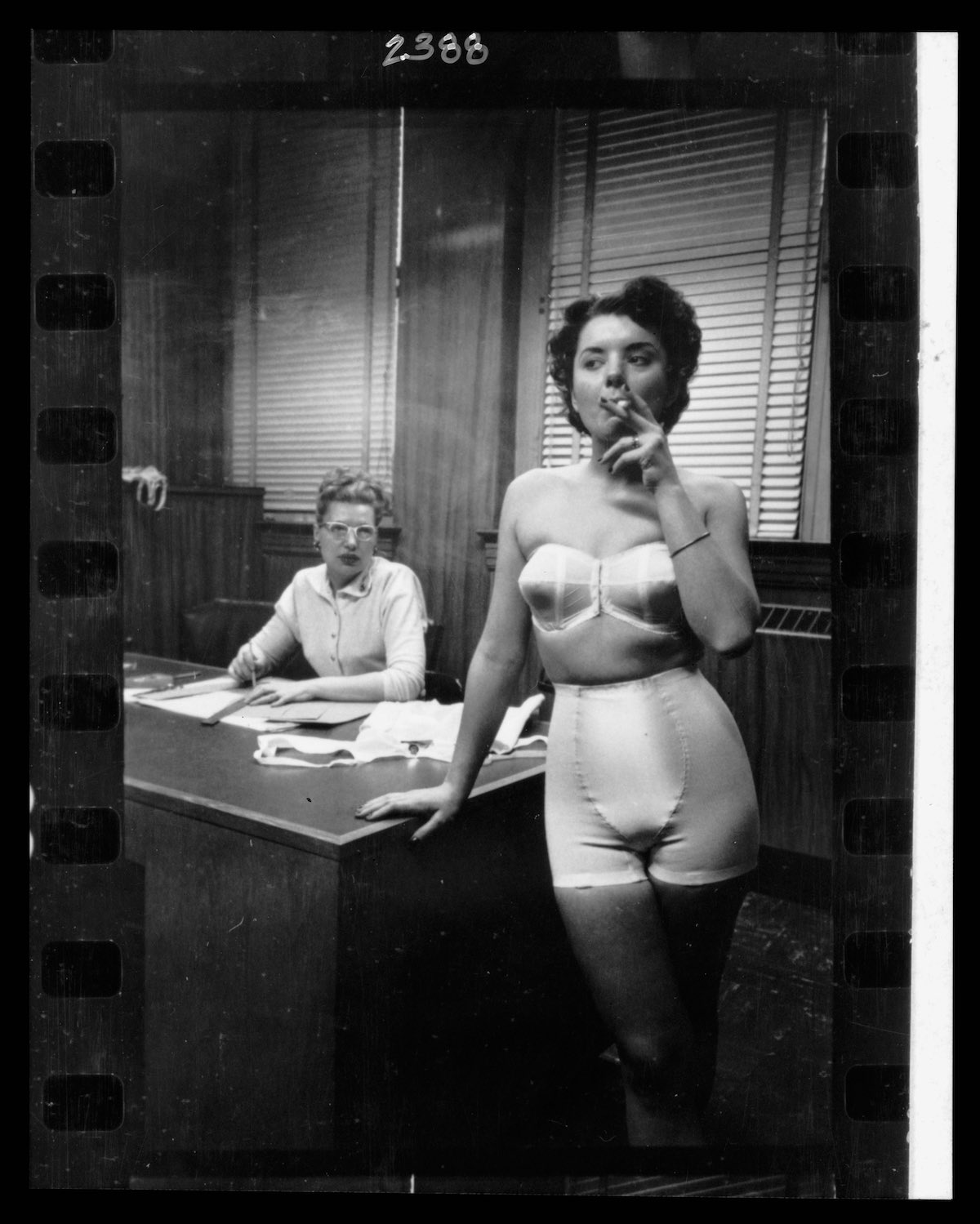 Lingerie model, wearing a girdle and strapless bra, smoking in an office; in the background a woman sits at a desk